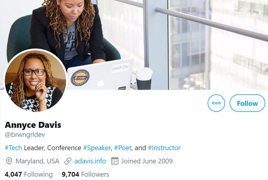 Instagram profile photo of Annyce Davis, Tech Leader, smiling in black-and-white pullover with her cover photo of her sitting in chair and working on computer